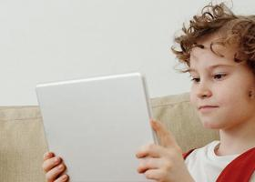 A child of around 10 years old siting on a sofa using a tablet computer