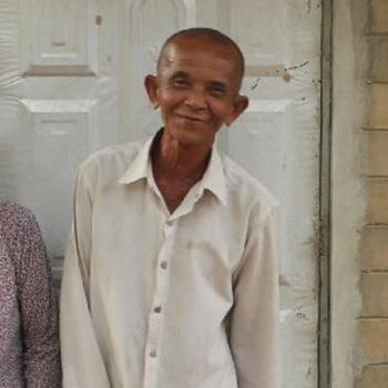 A man and woman standing in front of a toilet in rural Cambodia